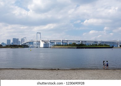 Tokyo, Japan - September 17, 2018 : View of two girls on Odaiba Beach overlooking the Rainbow Bridge during mid day at Odaiba