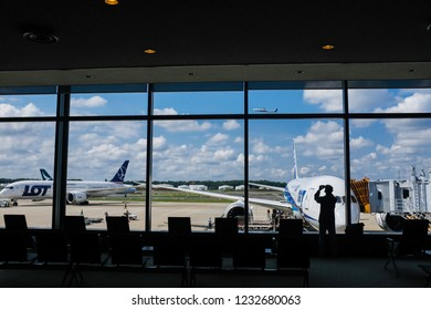 Tokyo, Japan - September 18, 2018 : View looking out to the airport tarmac with assorted aircraft, blue sky and clouds