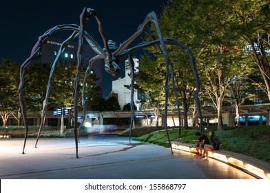 TOKYO, JAPAN - SEPTEMBER 18: A couple sit near the spider sculpture outside of Mori Tower in Roppongi Hills on September 18, 2013 in Tokyo, Japan.