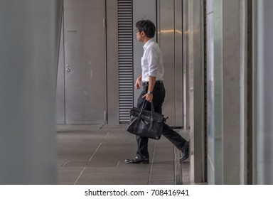TOKYO, JAPAN - SEPTEMBER 1ST, 2017. Japanese white-collar worker or salaryman walking to office in the morning.
