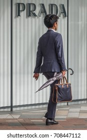 TOKYO, JAPAN - SEPTEMBER 1ST, 2017. Japanese salaryman walking in front of Prada luxury brand outlet in Tokyo Station.