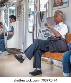 TOKYO, JAPAN - SEPTEMBER 1ST, 2017. Elderly man reading newspaper in Tokyo Metro subway train.