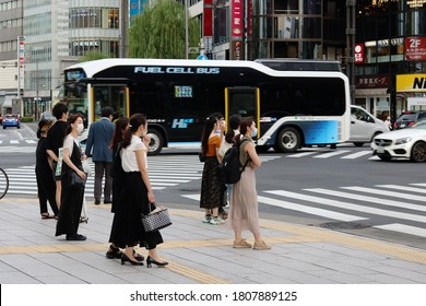 TOKYO, JAPAN - September 2, 2020: People wait to cross Sukiyabashi scramble crossing in Ginza as a fuel cell bus, a TOEI-operated Toyota FC Bus, passes. Some motion blur.