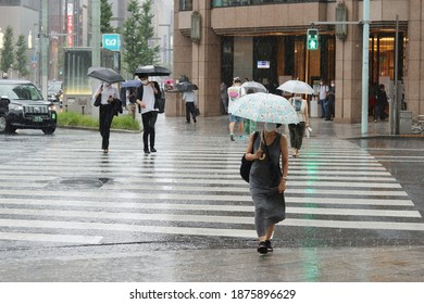 TOKYO, JAPAN - September 2, 2020: Photo taken in heavy rain focus on foreground of people using a crosswalk in Ginza during a heavy downpour. Mitsukoshi Department Store is in the background.