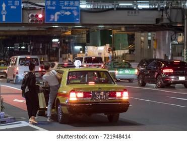 TOKYO, JAPAN - SEPTEMBER 23RD, 2017. Customers boarding a taxi in Shibuya street at night.