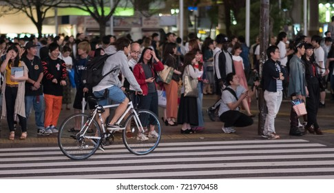 TOKYO, JAPAN -SEPTEMBER 23RD, 2017. People riding bicycle in the street of Shibuya at night.