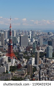 TOKYO, JAPAN - September 28, 2018: View of Tokyo and the Tokyo Tower seen from the Skydeck at the top of the 238m Roppongi Hills Mori Tower. Toyko Bay is visible in the distance.