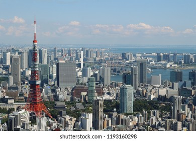 TOKYO, JAPAN - September 28, 2018: View of the Tokyo Tower and Tokyo's skyline seen from the Skydeck at the top of the 238m Roppongi Hills Mori Tower. Tokyo Bay is in the distance.