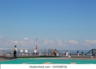 TOKYO, JAPAN - September 28, 2018: People on Skydeck, the observation deck at the top of the 238m Roppongi Hills Mori Tower. Skyscrapers and the top of the Tokyo Tower are visible in the background.