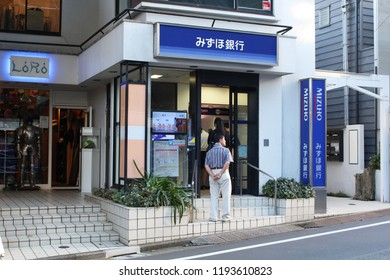 TOKYO, JAPAN - September 28, 2018: Customers waiting in line to use ATMs in a branch of Mizuho Banlk in the late afternoon in Tokyo's Daikanyama area.