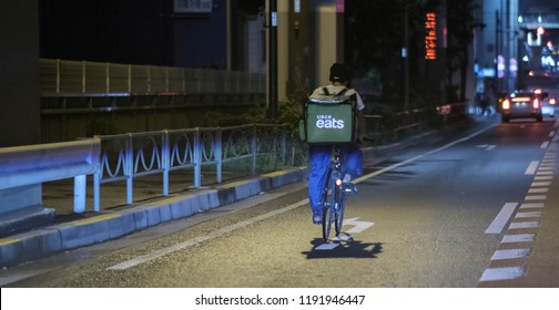 TOKYO, JAPAN - SEPTEMBER 28TH, 2018. Uber Eats rider riding bicycle in Meguro Streets at night.