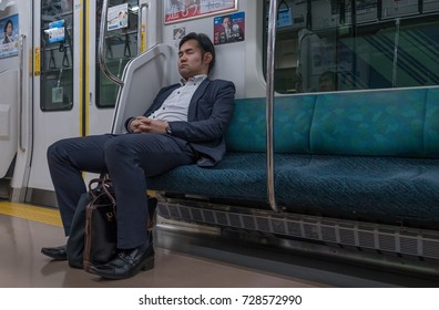 TOKYO, JAPAN - SEPTEMBER 29TH, 2017. A tired man in business suit sleeping in a Japan Railway train.