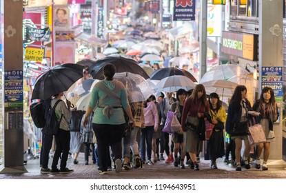 TOKYo, JAPAN - SEPTEMBER 29TH, 2018. Tourists and visitors with umbrellas walking at Takeshita Dori street of Harajuku during a rainy night.