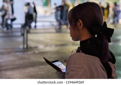TOKYO, JAPAN - SEPTEMBER 29TH, 2018. Japanese girl with a smartphone in Harajuku street at night.