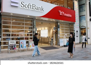 TOKYO, JAPAN - September 30, 2020: The front of a Softbank / Y!mobile store in Ginza. People wear face masks during the coronavirus outbreak. Some motion blur.