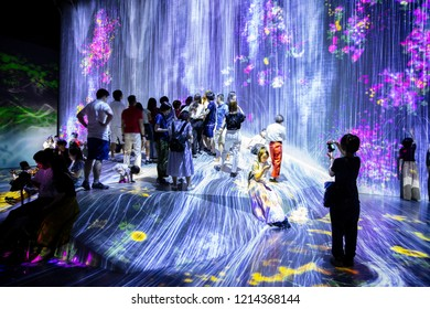 Tokyo, Japan - September 6, 2018: Visitors enjoying the 'rain' in one of the spaces within teamLab permanent exhibition in Mori Digital Art Museum.