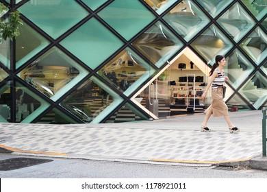 TOKYO, JAPAN - September 8, 2018: A pedestrian walks past the distinctive Herzog and de Meuron-designed Prada store in Aoyama.