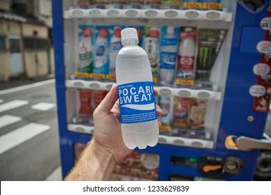 TOKYO, JAPAN - SEPTEMBER 8, 2018: Vending machines Pocari Sweat sports drink bottle held in hand. Beverage vending machines are widely spread over Japan