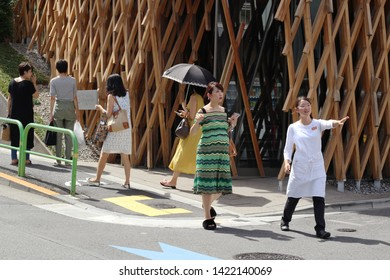 TOKYO, JAPAN - September 8, 2018: People on the street in front of the distinctive SunnyHills building, a pineapple cake shop in Minami-Aoyama. The basket-shaped building was designed by Kengo Kuma.