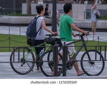 TOKYO, JAPAN - SEPTEMBER 8TH, 2018. Tourist couple with bicycles at Tokyo Railway Station plaza at dusk.