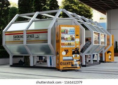 TOKYO, JAPAN - September 9, 2017: People using a smoking space in Tokyo Dome City. Next to it are drinks vending machines with special Tokyo Giants baseball-themed drinks livery.