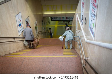 Tokyo / Japan - September 9, 2017: Japanese elder couple carrying baggages and walking down steps inconveniently at Tokyo train main station