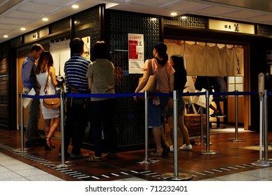 TOKYO, JAPAN - September 9, 2017: People waiting for a seat outside Ginza Kagari a popular ramen restaurant in Tokyo's Ginza subway station awarded Bib Gourmand status by the Michelin Guide.