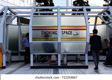 TOKYO, JAPAN - September 9, 2017: People using a smoking space in Tokyo Dome City. The structure is supported by JT (Japan Tobacco).