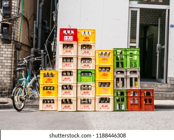Tokyo, Japan. September 9, 2018: A close up of stacks of plastic red, white, and yellow crates containing Asahi beer and soft drink bottles in Japan