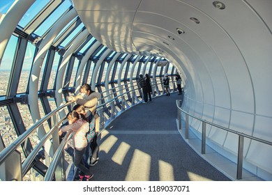 Tokyo, Japan-December 28, 2017: Tembo Galleria the sight platform in Skytree TV tower. Some people stand at the railing and observe Tokyo down below. The city runs behind horizon.