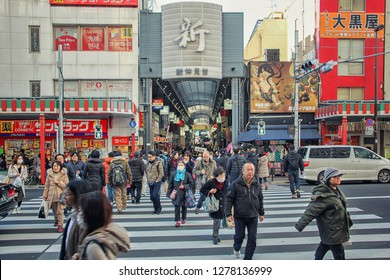 Tokyo, Japan-December 29, 2017: An entrance to the shopping arcade of famous tourist spot Asakusa, a crowd of people crossing the road and there are many shops in the background.