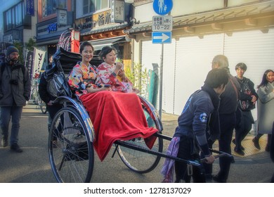 Tokyo, Japan-December 29, 2017: Traditionally dressed two Japanese women sit in rickshaw trolley. Puller pulls cheerful ladies about Asakusa district