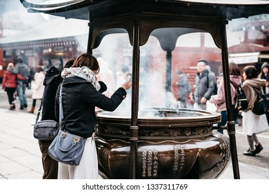 TOKYO, JAPAN-JAN 31, 2019:Unidentified man and woman covering themselves with smokes from the large incense burner at the Sensoji Temple. Asakusa Temple is one of Tokyo Landmark located in Asakusa.