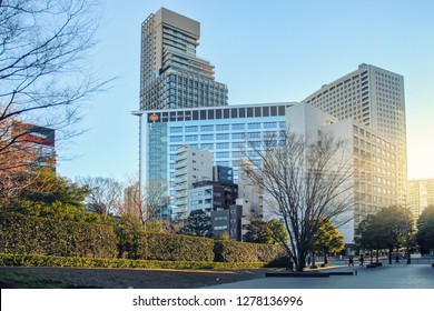 Tokyo, Japan-January 4, 2018: Broad streets with trimmed bushes on the side lead to Bandai Namco Group headquarter. A group of different height buildings with glass facades links with this corporation