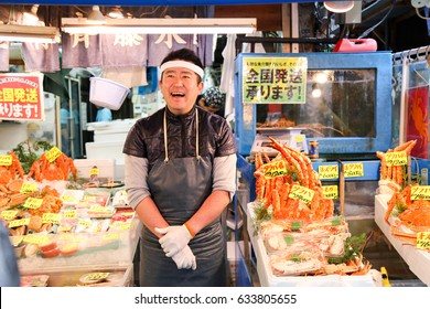 Tokyo, Japan-Nov 2016: Men selling fish have smiling face, impressing customer at Tsukiji fish market.