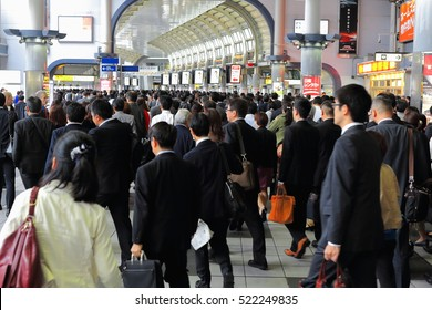 Tokyo, Japan-October 23, 2013: Hordes of salarymen along with career women and office ladies - terms for Japanese white-collar employees- daily assault the metro trains to go to work-Shinagawa station