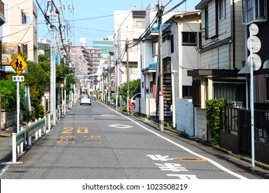 Tokyo, JP - AUGUST 10, 2017: Perspective asphalt street. Scenery of downtown residents that have buildings, electrical poles, traffic signs and one car on a street.