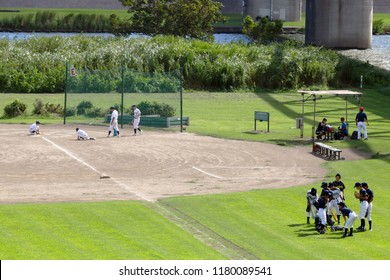Tokyo, JP - AUGUST 12, 2018: Group of junior high school's baseball team members playing their practice baseball games in the public outdoor baseball field near a riverside.