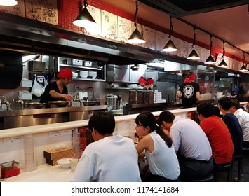 Tokyo, JP - AUGUST 15, 2018: A lot of customers sitting in front of the desk bar and eating their dinner in the Japanese noodle ramen restaurant.