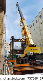 Tokyo, JP - JULY 4, 2017: The yellow crane taking the rusty steel chassis up for building frame at engineering site.