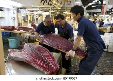 TOKYO- JULY 4: Workers processing Tuna at the Tsukiji Wholesale Seafood and Fish Market in Tokyo Japan on July 4, 2011. Tsukiji Market is the biggest wholesale fish and seafood market in the world.