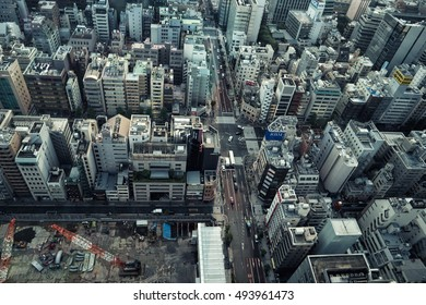 Tokyo - June 2016: Aerial city view with buildings, roads with traffic and construction site.