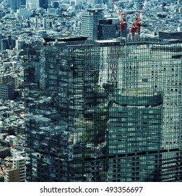 Tokyo - June 2016: Elevated city view with reflection of skyscrapers in glass building . Shinjuku