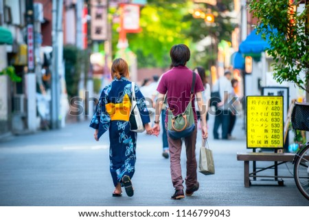 Tokyo, Kanto / Japan - July 3rd 2014: A couple is walking in the streets of Asakusa wearing traditional Japanese Kimono in summer 2014.