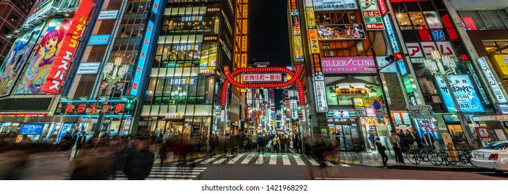 Tokyo - March 15, 2019 : Panoramic view of Motion blured people walking through the entrance of Kabukicho entertainment and Red Light district in Shinjuku Ward, Tokyo