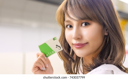 TOKYO - MAY 1016: Japanese girl shows Suica Card. The Suica can be used on JR East lines.