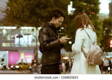 TOKYO - NOVEMBER 23, 2017: A dating couple standing by the Shibuya Crossing and exchanging phone numbers. Shibuya Crossing is rumoured to be the busiest intersection in the world.