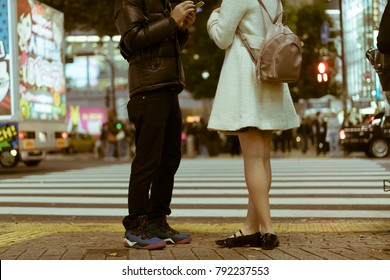 TOKYO - NOVEMBER 23, 2017: Low angle view of a dating couple standing by the Shibuya Crossing and exchanging phone numbers. Shibuya Crossing is rumoured to be the busiest intersection in the world.