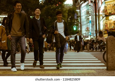 TOKYO - NOVEMBER 23, 2017: Three male high-school students crossing the Shibuya Crossing and laughing. Shibuya Crossing is rumoured to be the busiest intersection in the world.