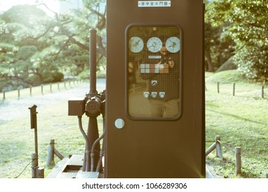 TOKYO - NOVEMBER 24, 2017: Vintage sluice tracker located in Hamarikyu Gardens. The label on the machine reads: 'Koshin-temple sluice'. A sluice is a water channel controlled at its head by a gate.